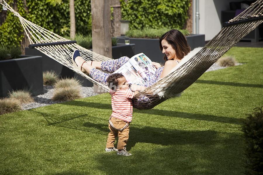 Együtt a család az udvaron, kellemes délután a műfű padló szőnyegen ücsörögve. A kényelmes és esztétikus műfű egyszerre több funkcióval bír.